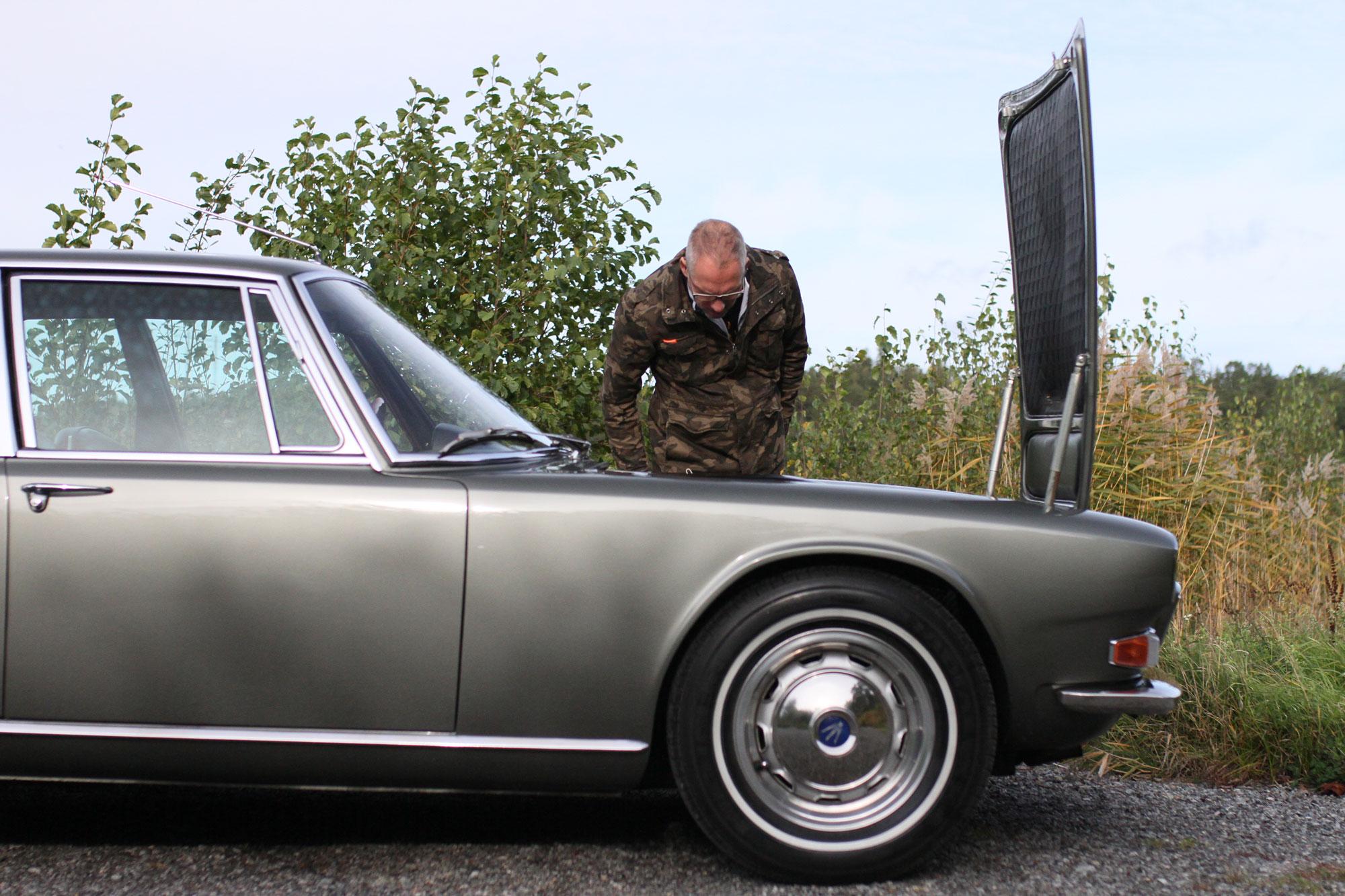 Fredric Gustafsson tittar ner i MAserati QUattroportens motorutrymme. Höger fram av bilen.