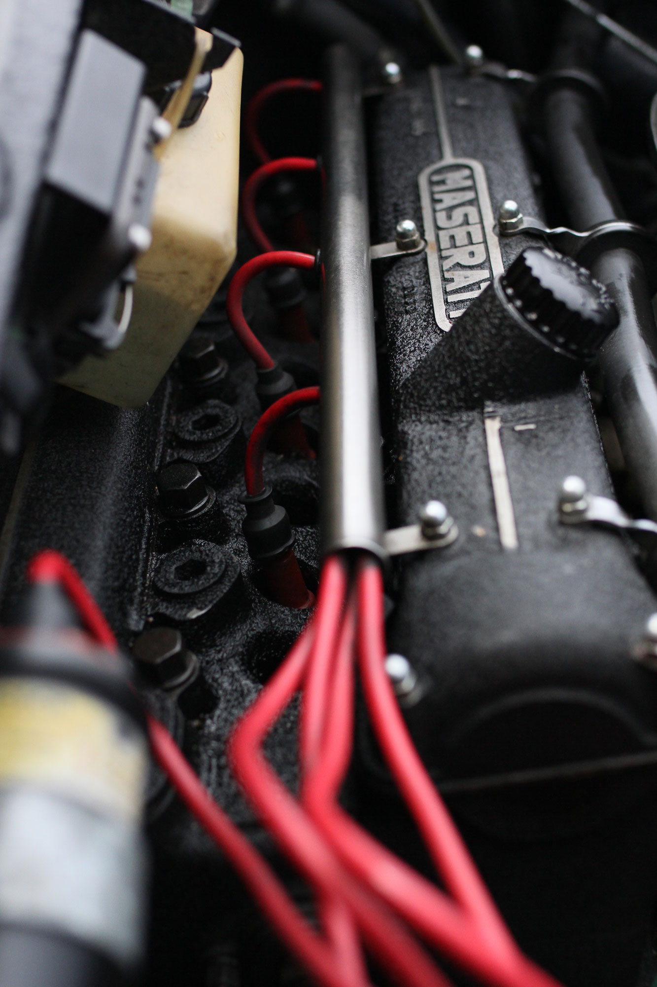 Black cylinder block with Maserati text on, and red ignition cables with extra holes sparkplugs holes