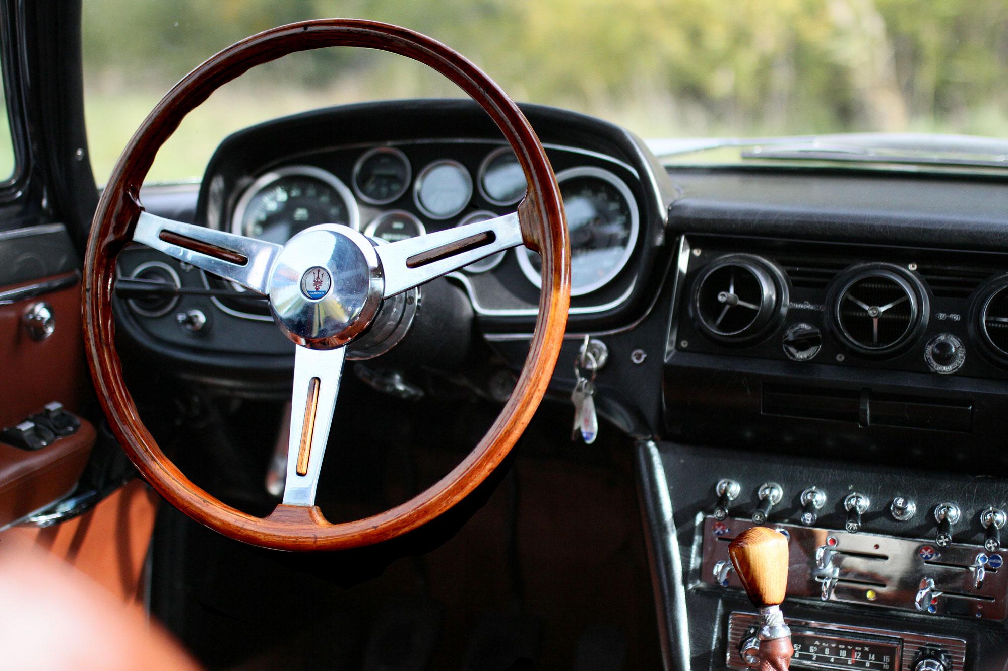 Inbjudande förarplats med vacker trärätt och inbjudande inredning i en klassisk Maserati Quattroporte