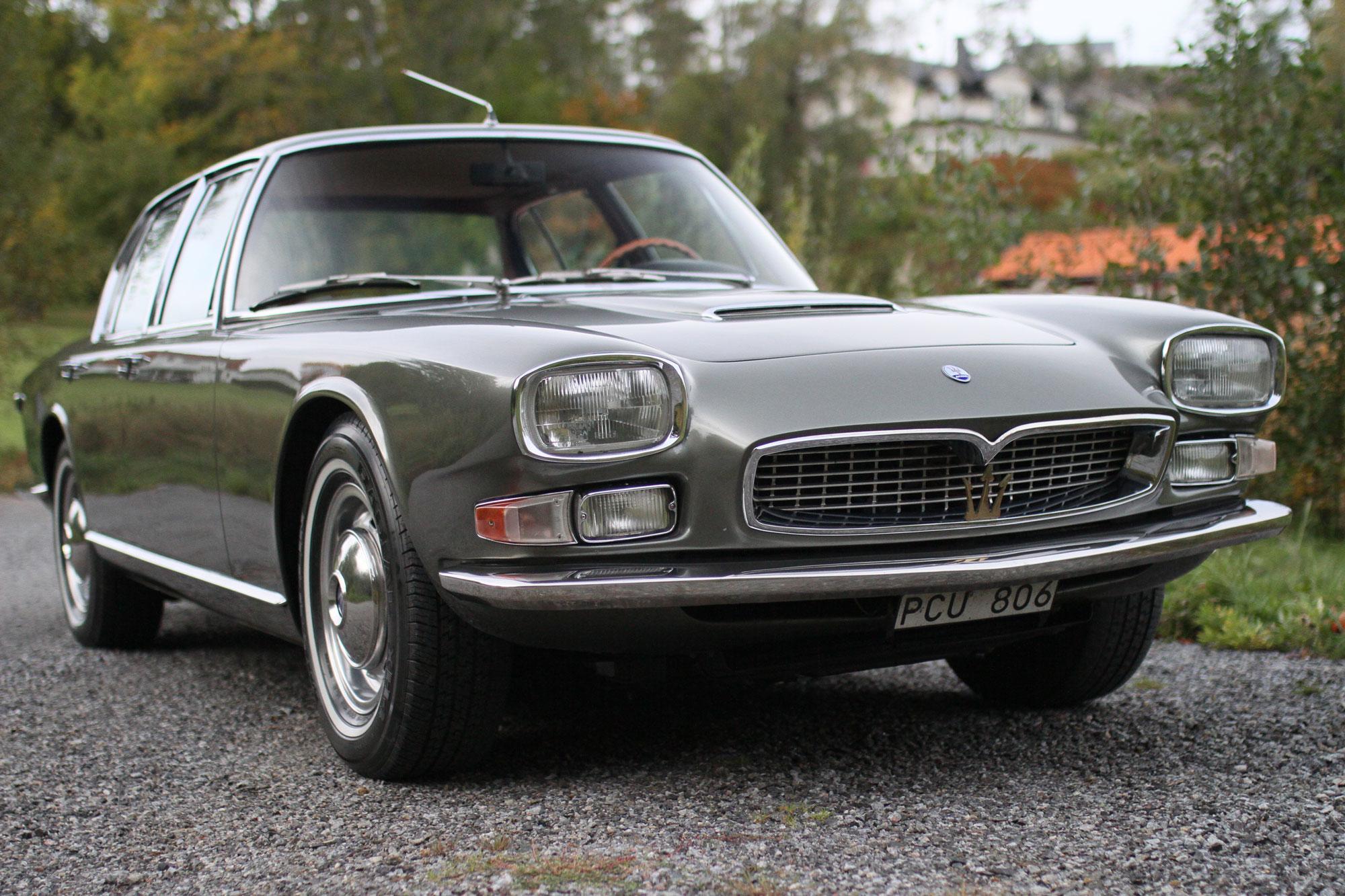 Maserati Quattroporte höger framifrån på en grusväg med ett tegeltak i bakgrunden. Fyrkantiga strålkastare