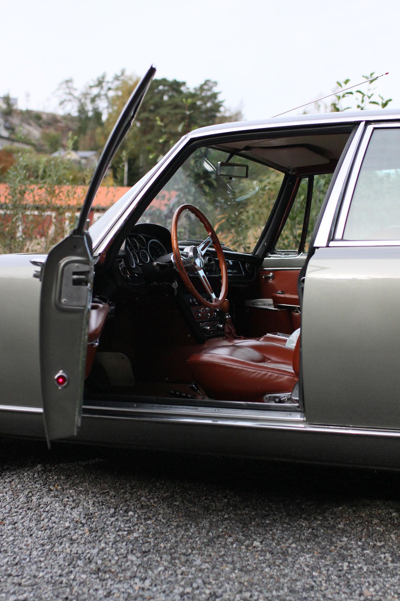 Maserati Quattroportes förardörr är öppen. Inbjudande bild till förarmiljön med träratt