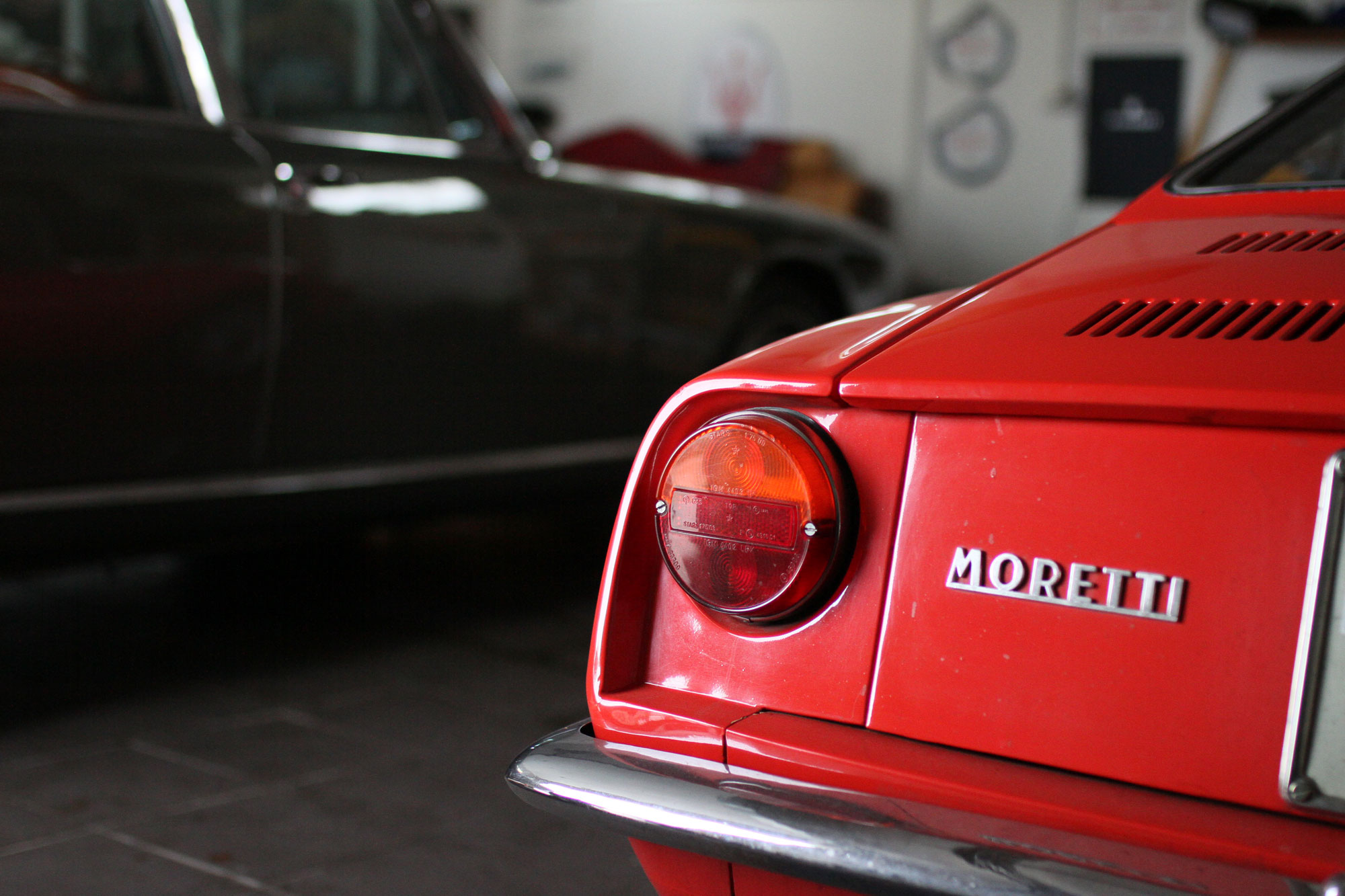 Moretti 850 from behind with Quattroporte behind, next to the garage