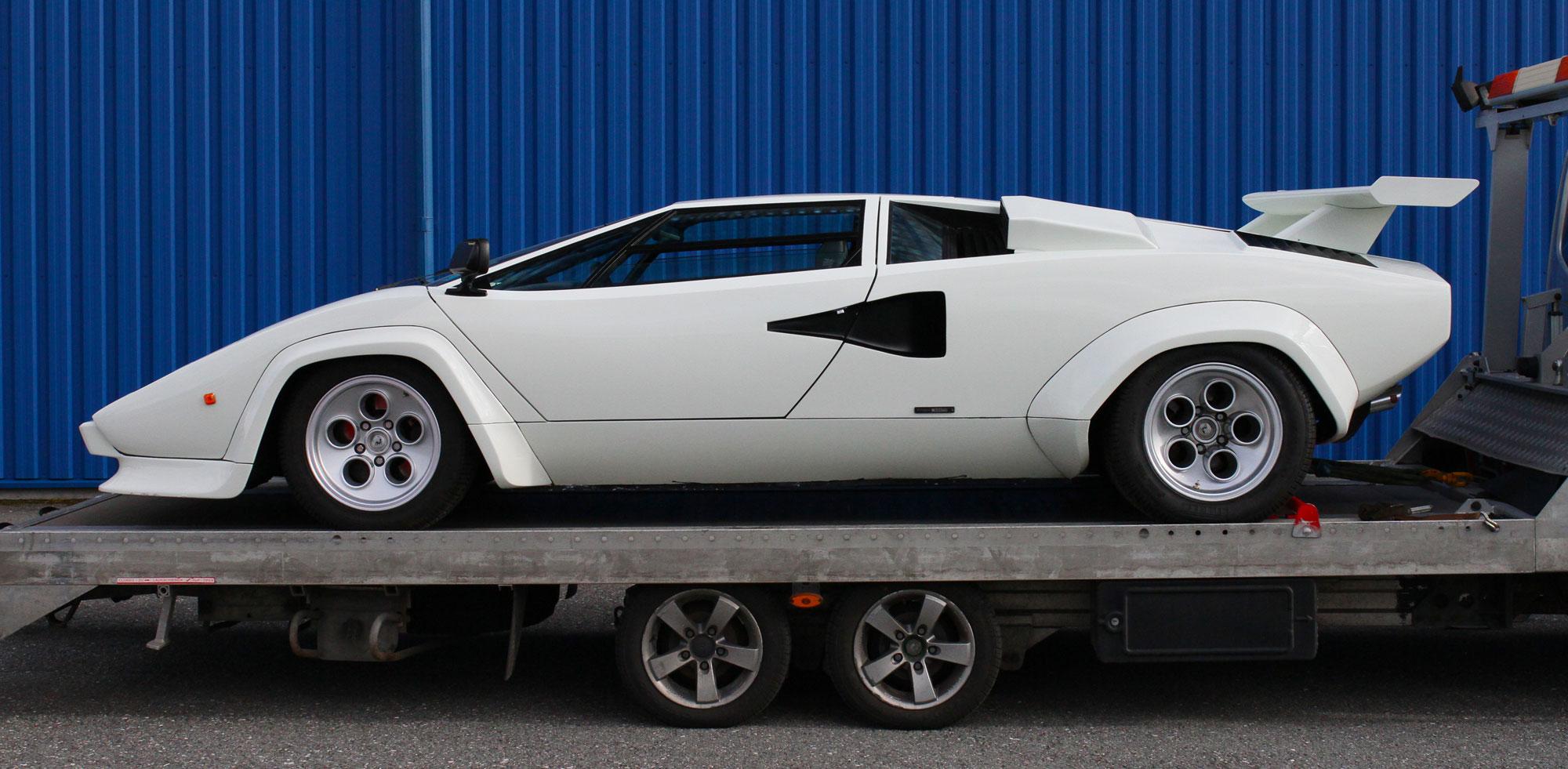Lamborghini Countach ståendes på en bärgare utanför den blåa lokalen