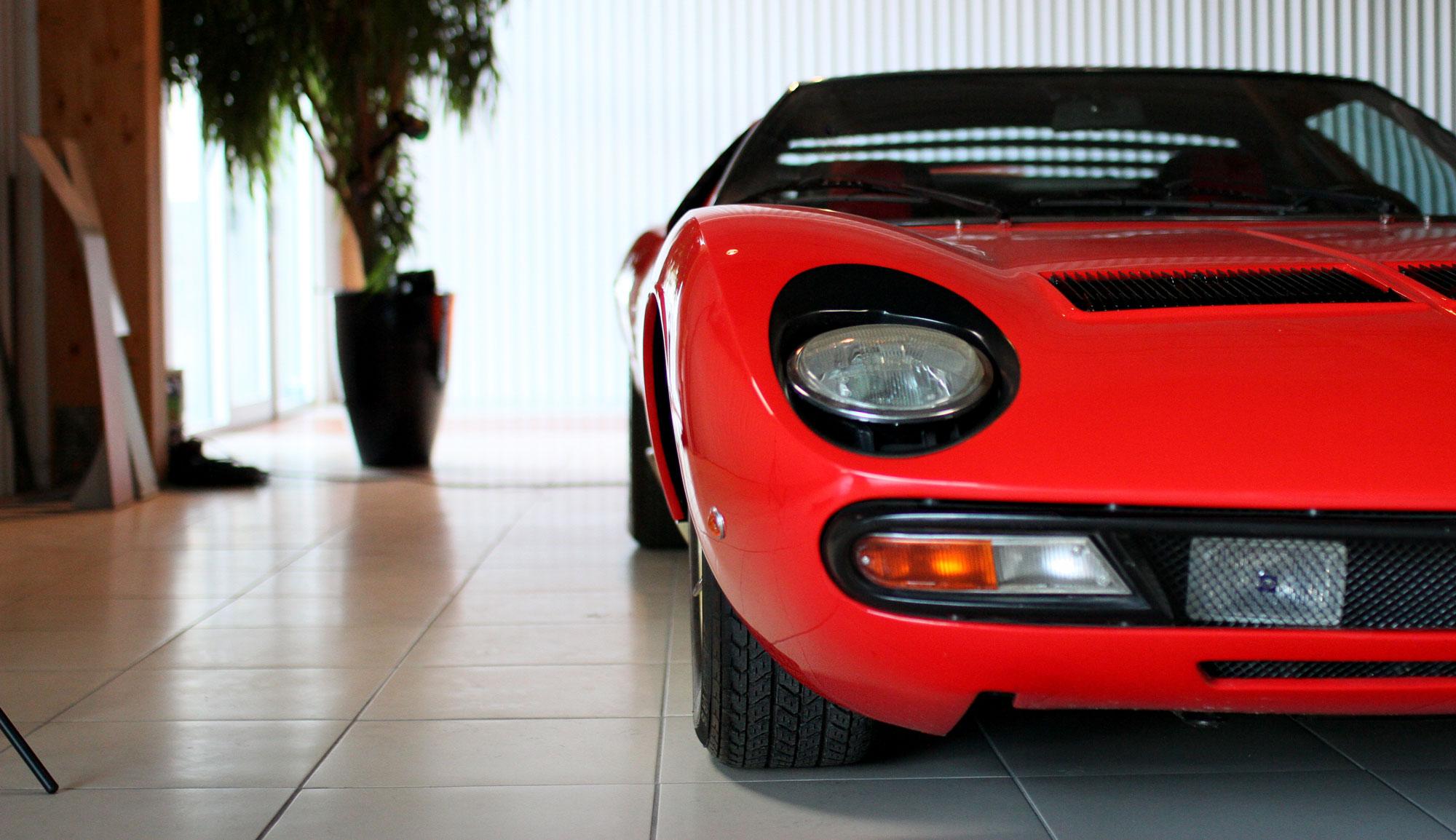 Lamborghini Miura LP400S Röd i garaget med ett svart kamera stativ stickandes fram
