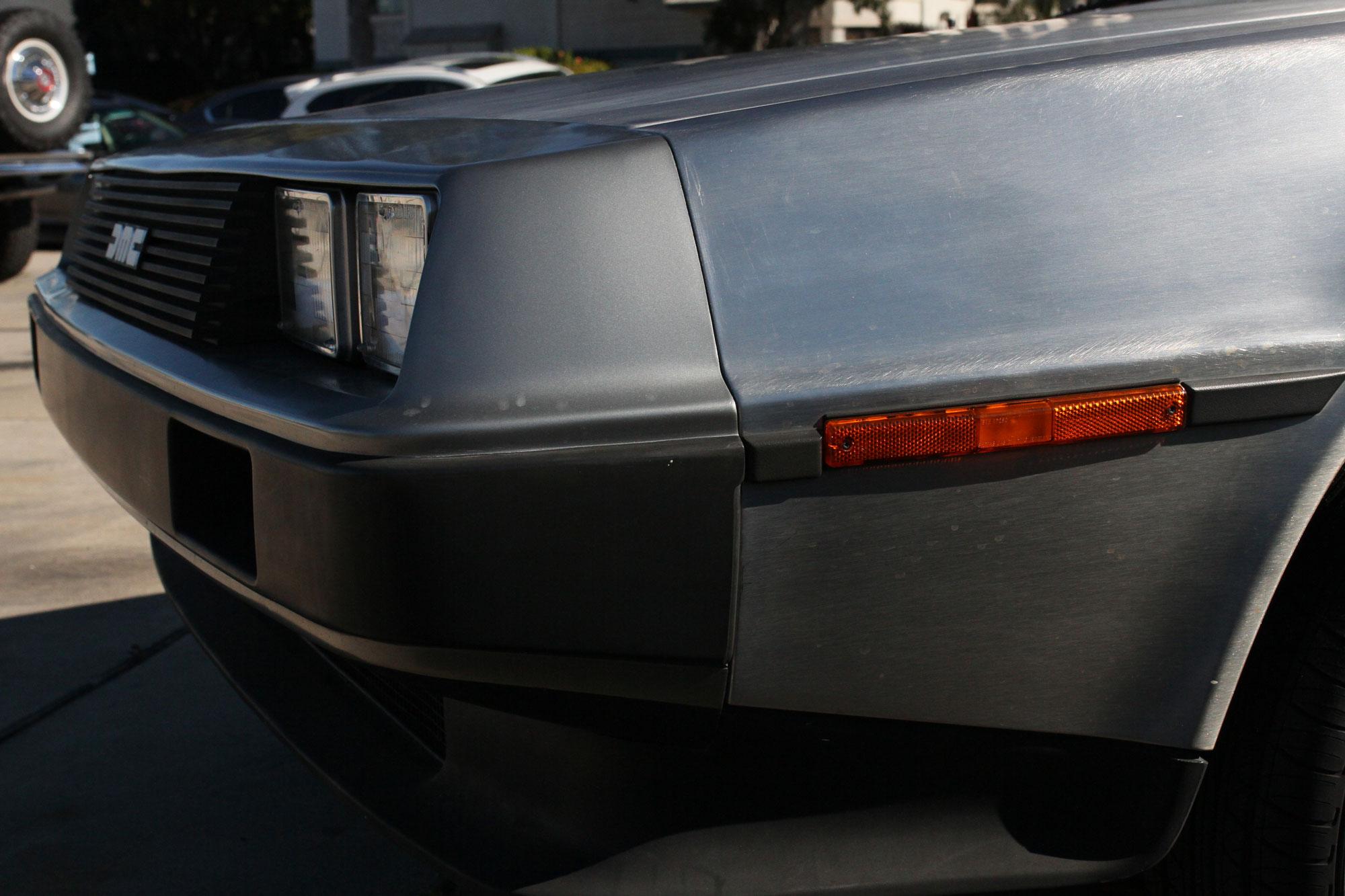 vänster front av DeLorean 1981 utanför Garage 77 med Ford Bronco i bakgrunden