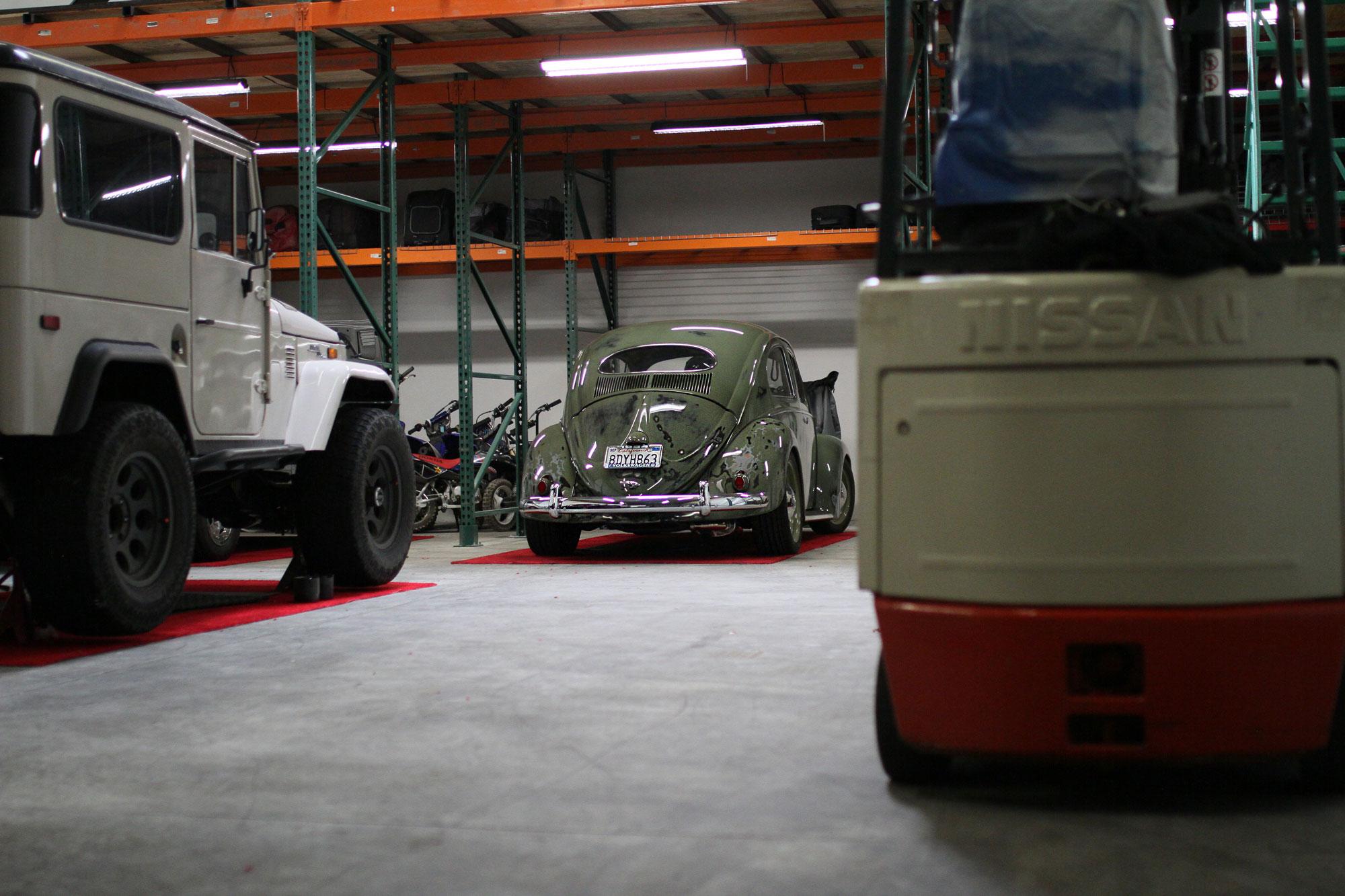 Grön VW bubbla med klarlack och en vit Toyota FJ40 i ett Los Angeles Garage